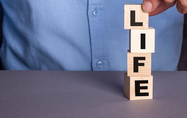 Um homem de camisa azul compõe a palavra vida em cubos de madeira verticalmente.
