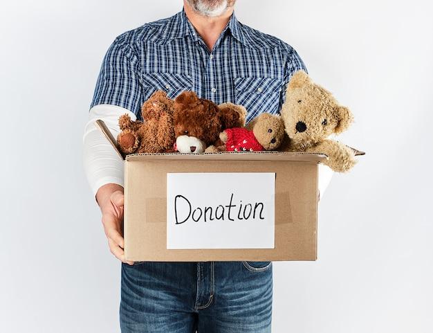 Um homem de camisa azul e jeans, segurando uma grande caixa de papel marrom com brinquedos para crianças