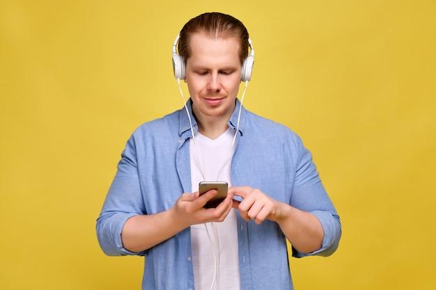 Um homem de camisa azul em um fundo amarelo em fones de ouvido brancos ouve música e alterna músicas em um smartphone.
