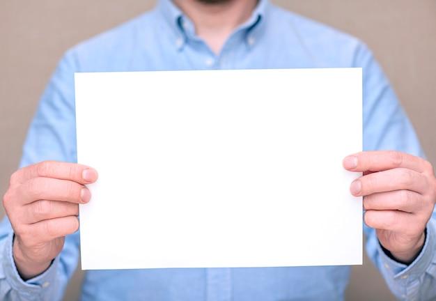 Um homem de camisa azul, empresário segurando uma folha branca em branco. espaço para texto, maquete