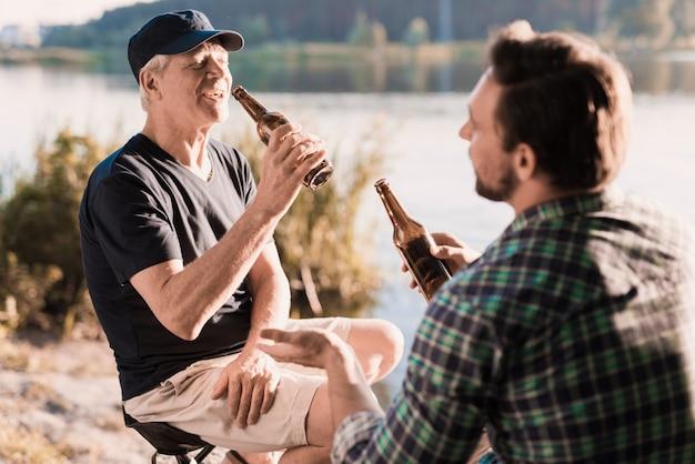 Um homem de camisa azul está bebendo cerveja no rio