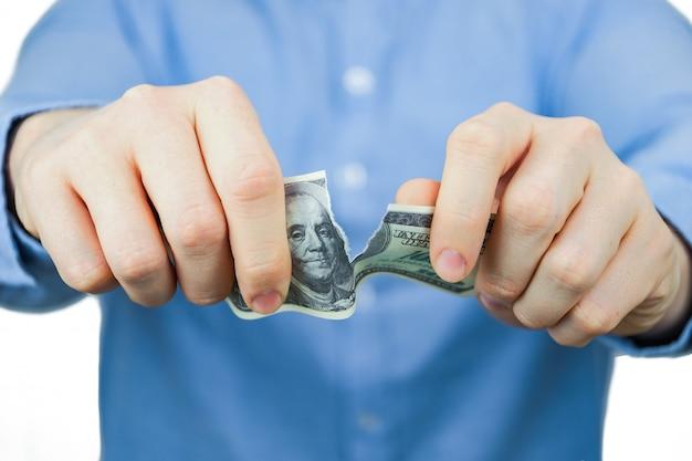 Um homem de camisa azul segura cem dólares e os rasga.