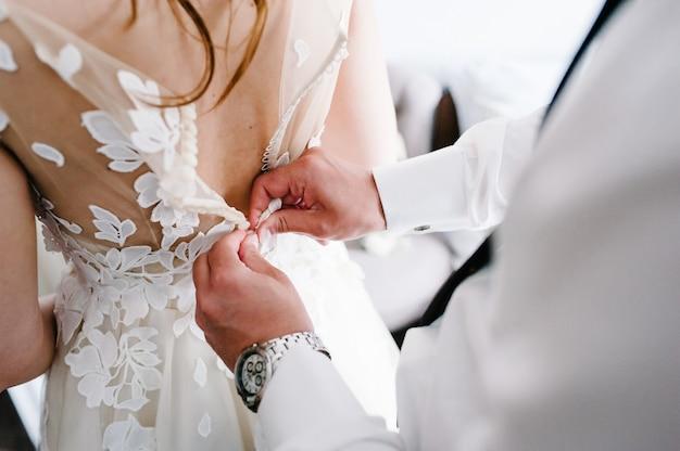 Um homem de camisa branca, gravata e relógio fecha os botões do espartilho do vestido. noiva vestida de noiva com laço em pé na sala.
