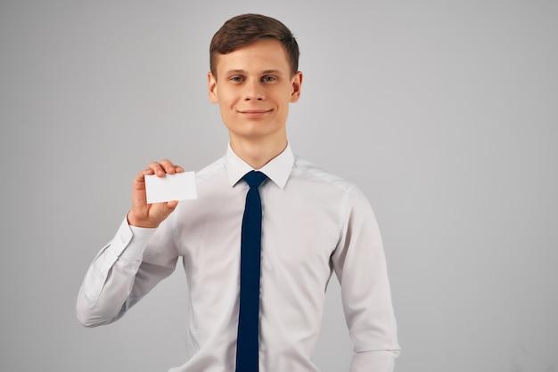 Um homem de camisa e gravata segurando um cartão de visita publicitário