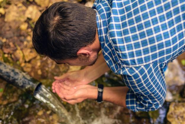 Um homem de camisa em uma gaiola coleta água fresca de uma fonte nas mãos postas, bebe água de uma fonte