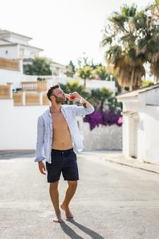Um homem de camisa listrada, caminha pelas ruas de uma pequena cidade espanhola.