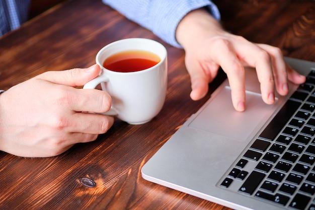 Um homem de camisa toma chá e navega na web em um laptop.