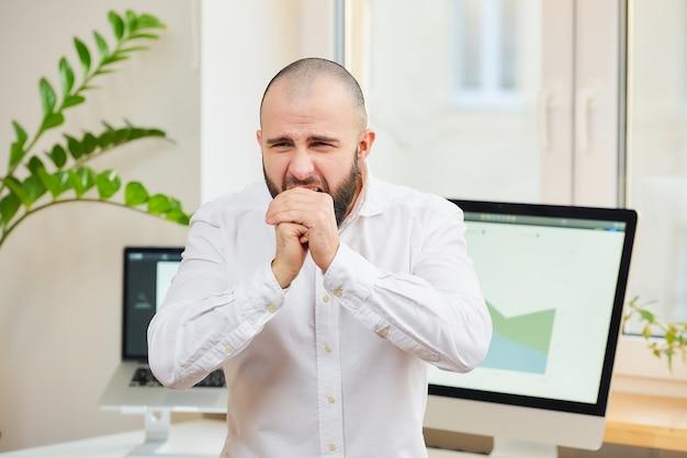 Um homem de camisa tossindo nas mãos