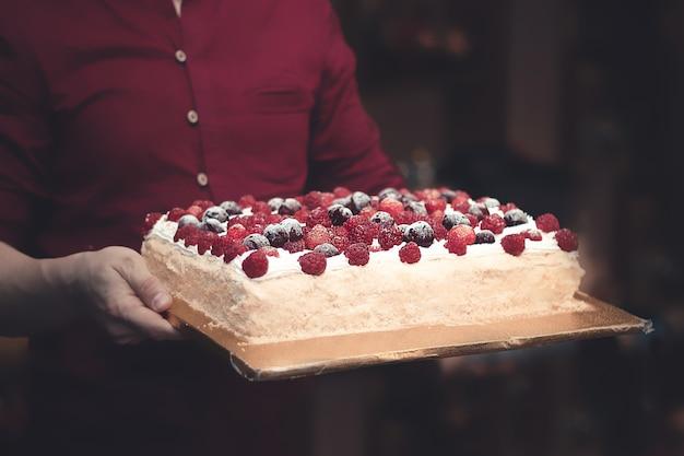 Um homem de camisa vermelha carrega uma torta de frutas vermelhas nas mãos sobre um fundo escuro em um café.