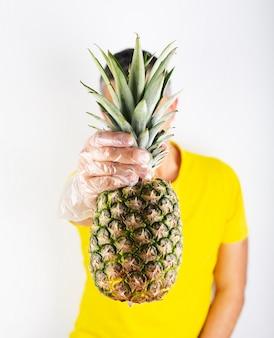 Um homem de camiseta amarela usa luvas de supermercado e ananás. compra de segurança