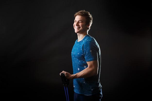 Um homem de camiseta azul de pé e sorrindo com equipamento de fitness na mão