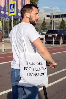 Um homem de camiseta branca e com uma bolsa no ombro anda pela cidade em uma scooter elétrica