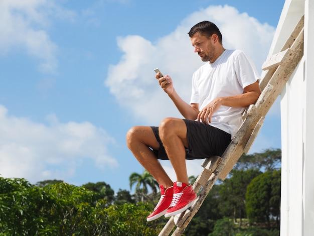 Um homem de camiseta branca e tênis vermelho se senta em uma escada de madeira e usa um telefone celular.