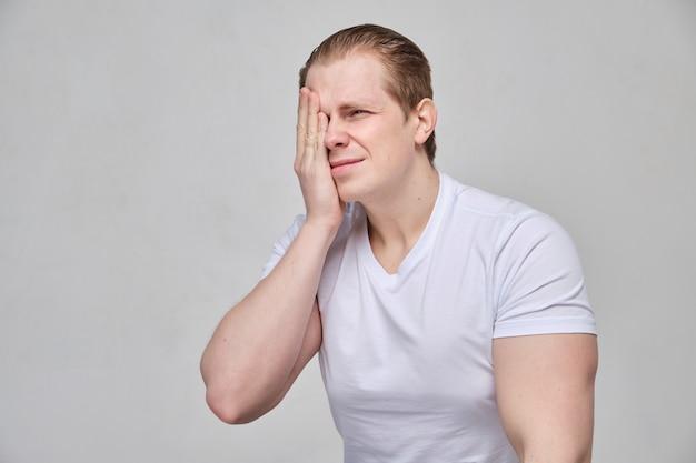 Um homem de camiseta branca massageia o olho - uma dor terrível devido a inflamação.