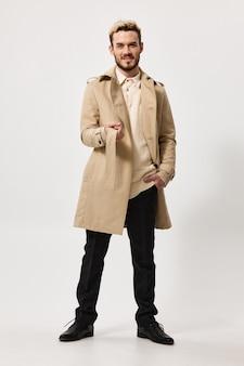 Um homem de casaco e calças escuras caminha para o lado sobre uma tendência de fundo claro da modelo da estação