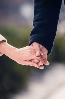 Um homem de casaco preto segura a mão de uma garota em um encontro