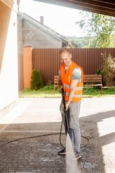 Um homem de colete laranja limpa um ladrilho de grama no quintal, perto da casa.