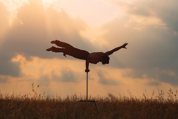 Um homem de constituição atlética realiza exercícios de ginástica complexos em um campo ao pôr do sol