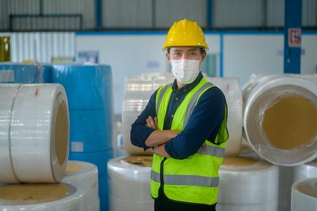 Um homem de engenharia usando máscara médica e capacete protetor trabalhando em uma fábrica de depósito