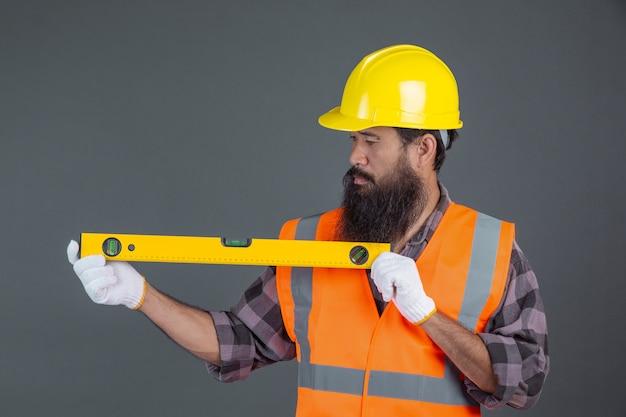Um homem de engenharia usando um capacete amarelo segurando um medidor de nível de água em um cinza.