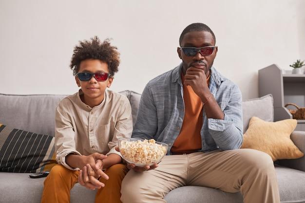 Um homem de família afro-americano moderno e seu filho adolescente sentados no sofá da sala assistindo a um filme em 3d e comendo pipoca