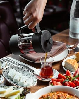 Um homem, de frente, servindo chá na refeição de café da manhã com chá de vidro