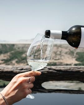 Um homem, de frente, servindo vinho em uma taça feminina, na cidade, vendo o álcool, pessoas humanas, vinho