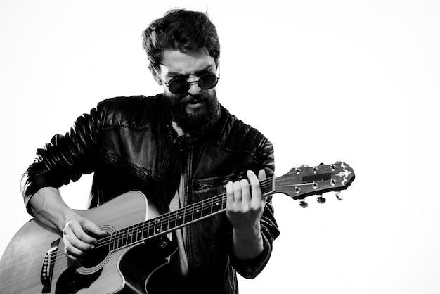 Um homem de jaqueta de couro e morena segura um violão nas mãos