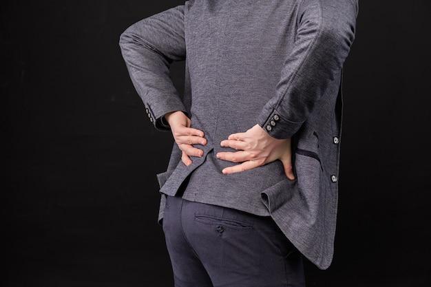 Um homem de jaqueta massageia a região lombar com as mãos sobre um fundo preto.