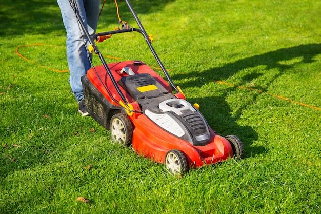 Um homem de jeans corta a grama no jardim com um cortador de grama no dia de verão