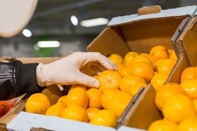 Um homem de luvas brancas em uma loja compra comida. homem tem uma laranja nas mãos