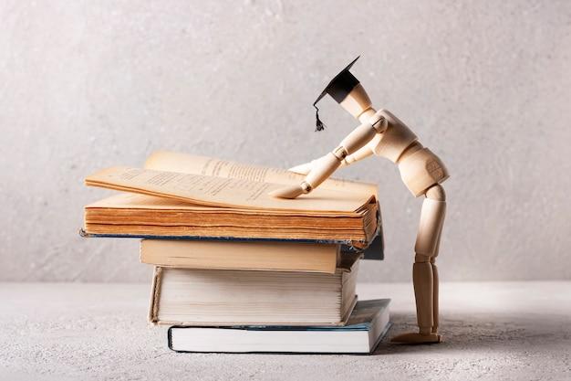 Um homem de madeira com um chapéu de estudante lê um livro didático