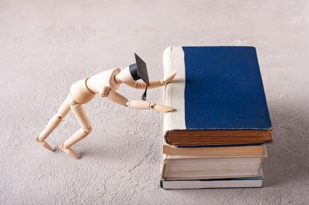 Um homem de madeira com um chapéu de estudante move uma pilha de livros didáticos