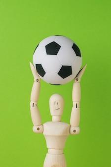 Um homem de madeira segurando uma bola de futebol na cabeça em um fundo verde.