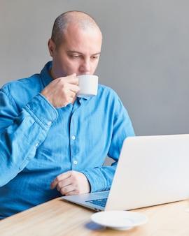 Um homem de meia idade bonito bebe café da caneca e olha para a tela de um computador, laptop.
