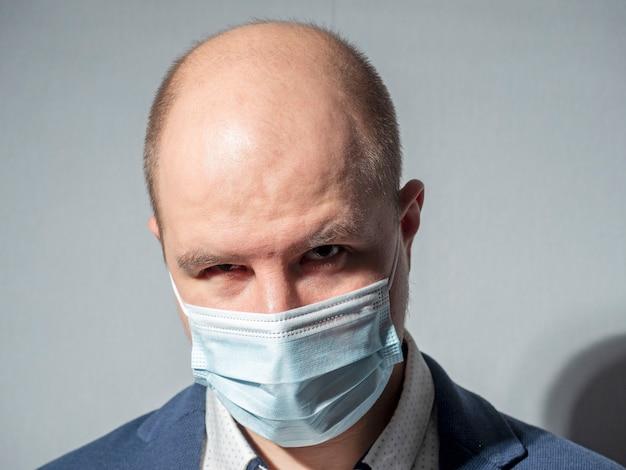 Um homem de meia-idade de terno. retrato, máscara médica. vista por baixo da sobrancelha
