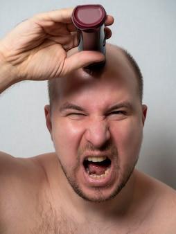 Um homem de meia-idade está diante de um espelho, raspa a cabeça com um barbeador elétrico e grita.