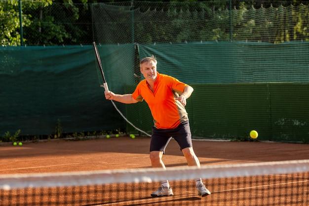 Um homem de meia idade joga tênis em uma quadra com uma superfície natural da terra em um dia ensolarado de verão.