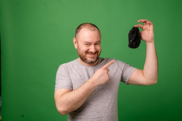 Um homem de meia-idade mostra uma meia suja em um fundo verde. lavanderia, higiene, conceito de pés fedorentos.
