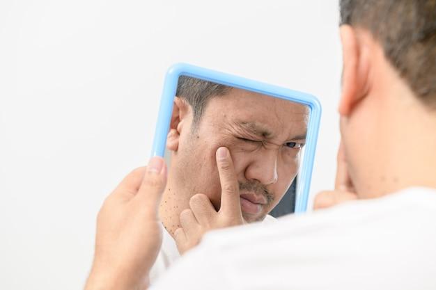 Um homem de meia-idade olhando no espelho e preocupado com manchas e rugas em seu rosto na parede branca, conceito de saúde