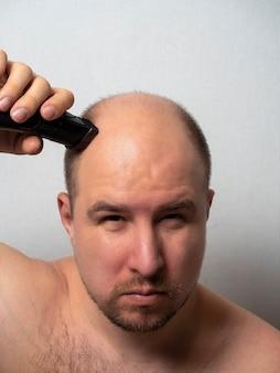 Um homem de meia-idade se olha no espelho e raspa a cabeça com um barbeador elétrico