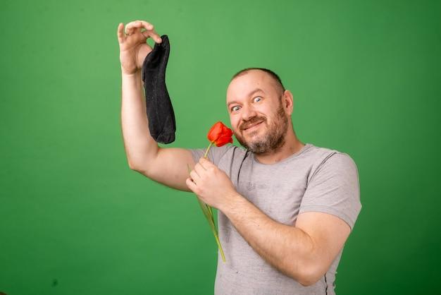 Um homem de meia idade segurando uma meia suja e fedorenta e uma flor fresca sobre um fundo verde. lavanderia, higiene, conceito de pés fedorentos.