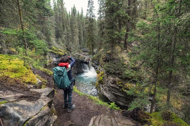 Um homem de mochila às costas tira uma foto com uma cachoeira no desfiladeiro johnston no parque nacional de banff, canadá