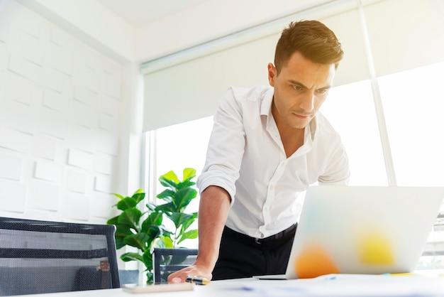 Um homem de negócio que trabalha seriamente com o portátil no escritório.