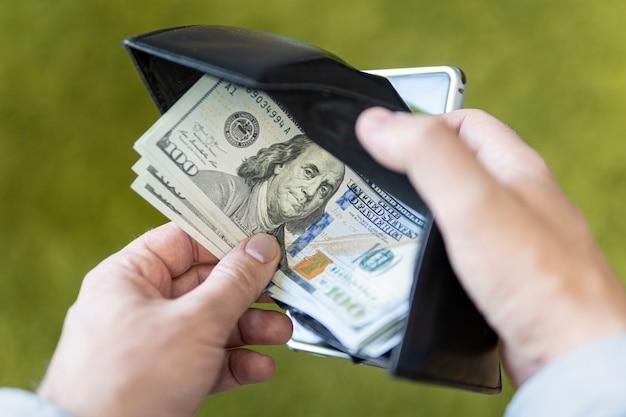 Um homem de negócios abre uma carteira preta e tira uma nota de cem dólares sobre um fundo verde. salário do empregado. bolsa com dólares nas mãos.