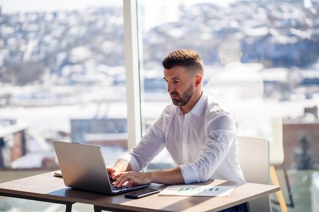Um homem de negócios adulto bem sucedido se senta em seu escritório com grandes janelas e trabalha em um laptop, trabalhando em novos projetos.