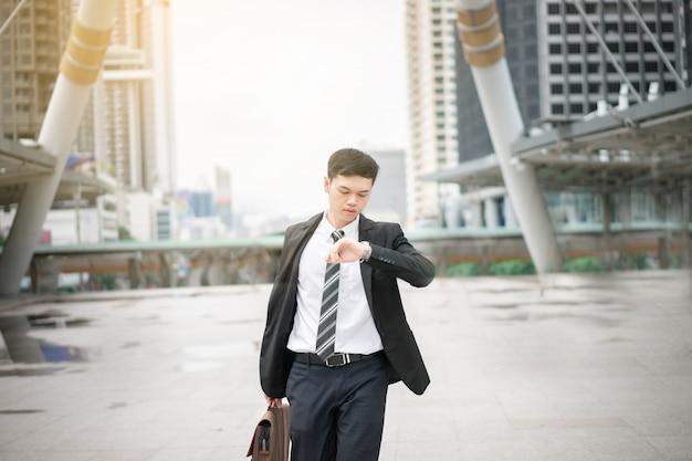 Um homem de negócios asiático vai funcionar. ele está na hora do rush. seu escritório fica na cidade de bangkok.
