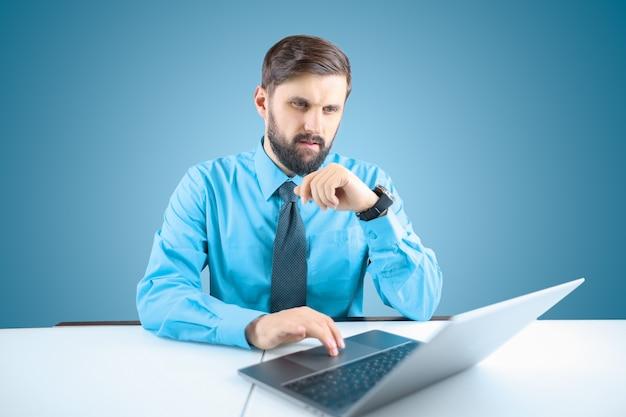 Um homem de negócios barbudo toca o trackpad atrás de seu laptop com o dedo