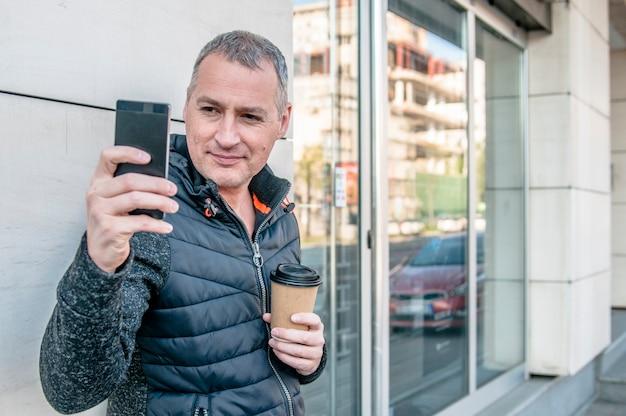 Um homem de negócios de meia idade andando ao lado do prédio de escritórios enquanto usa seu smartphone. empresário profissional casual urbano usando smartphone