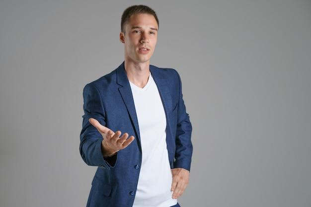 Um homem de negócios em um casaco azul em um fundo cinza gesticula para o lado, copie o espaço